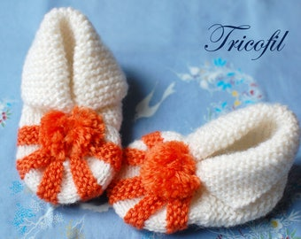 Orange and white baby booties hand knitted