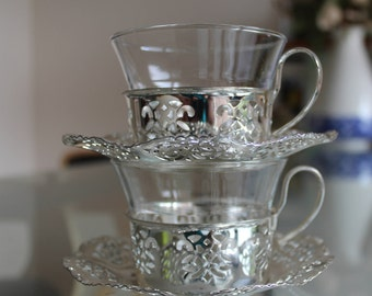 Two silver plated tea glasses and saucers, German origin.