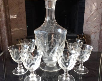 A decanter and 6 glasses in antique glass