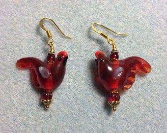 Translucent dark red lampwork songbird bead dangle earrings adorned with dark red Czech glass beads.