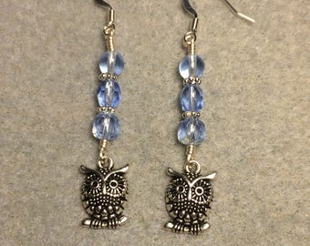 Silver owl charm dangle earrings  adorned with light blue Czech glass beads.