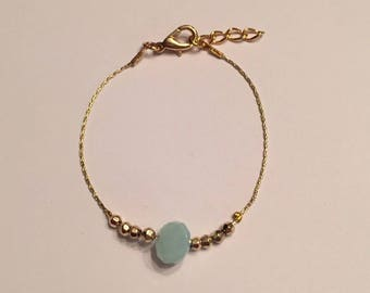 Gold Bracelet and bead in the Center with a blue bead
