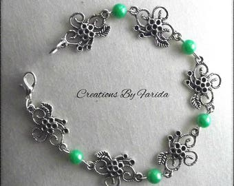 Bracelet curb chain with connector in the shape of flower and green beads