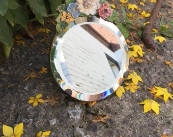 Beautiful round Bevelled freestanding mirror with lovely flower crest - perfect to add to a collection.