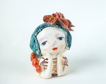 Porcelain girl figurine with blue hair and red  flowers. Ceramics