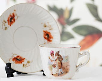 An antique small thin porcelain teacup, depicting a victorian couple and delicate orange poppies on a white porcelain base.