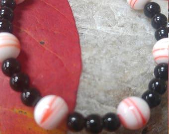Black  and Orange Glass Beaded bracelet, Black, orange white bracelet. Benefits Dog Rescue. Cat rescue.