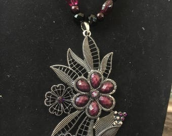 Purple beaded necklace with flower pendant and earrings