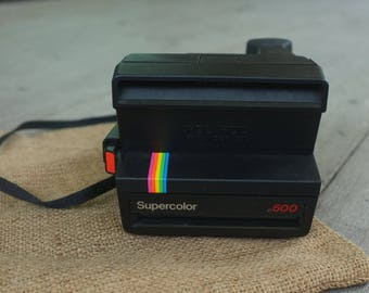 vintage Polaroid Supercolor 600 instant camera, black with camera strip.