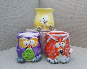 handmade pottery egg-cup cats, owls and foxes in yellow, purple & orange