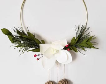 Modern crepe paper winter wreath featuring a magnolia flower, red berries, pine branches and bleached pinecones