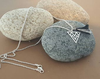 silver necklace with triangular pendant and tassel
