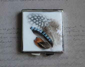 Pill box or small square box, 4 compartments, covered with resin and 3 feathers