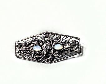 Edwardian brooch in silver tone with moonstones and center rhinestone.