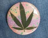 Pressed Cannabis Leaf Button On Pink, Orange & Purple Background