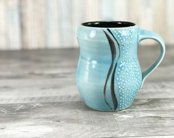 Curvy mug: handmade blue mug with curvy lines and dotted texture. Sky blue glazed mug, black interior. Porcelain mug. Pottery mug. Unique.