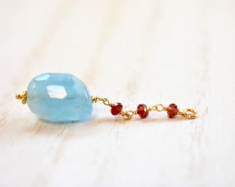 natural aquamarine focal pendant necklace with garnet detail. gold filled chain. freeform faceted aquamarine pendant necklace. blue focal