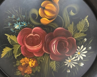 Round Floral Black Tole Tray with Beautiful, burgundy, gold, and blue hand painted flowers with gold rim. Signed by Sellea.