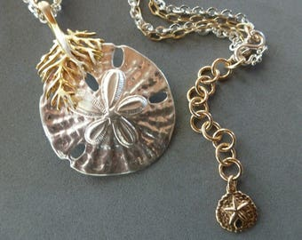 Sand Dollar Necklace mounts a delicate silver sand dollar on a golden coral bail and gold and silver chain for a glamorous beachy find!