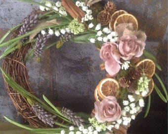 dried and artificial flower arrangement ,subtle pink and muted earth colours.Garland wall hanging design