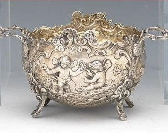 Antique & Marked Deep Silver bowl with handles, raised on four scroll legs, relief decorated with angels, birds and floral -- German Origin