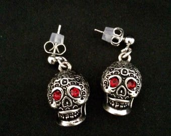 Pair Of Earrings Featuring Day Of The Dead Style Skulls With Sparkling Red Jeweled Eyes