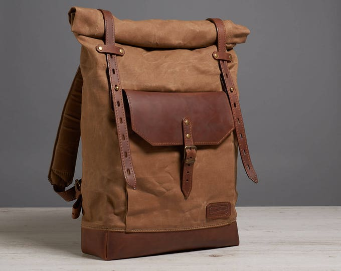 Brown waxed canvas roll-top backpack.