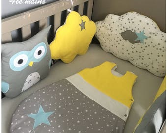 Baby bumper in the shape of owls and gray, yellow and white clouds with stars