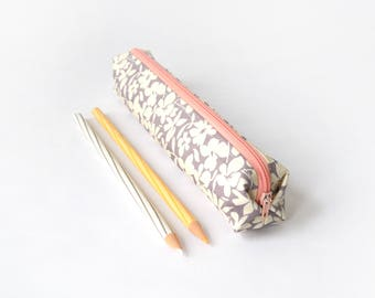 Small pencil case/zipper pouch with off-white flowers on a light grey background, with a pale pink zip