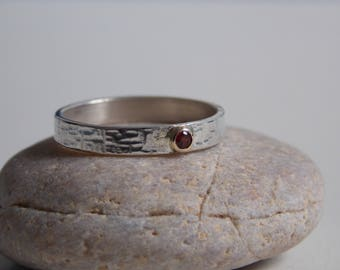 Hammered silver effect ring with an orange Garnet surrounded with a crimp yellow gold.