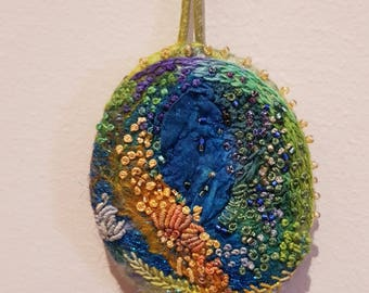 Hand-dyed silk and wool pendant, embellished with embroidery floss and beads.