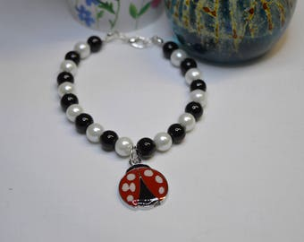 faux pearl bracelet with ladybird charm