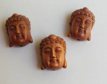 Four (4) Buddha heads wood and bone