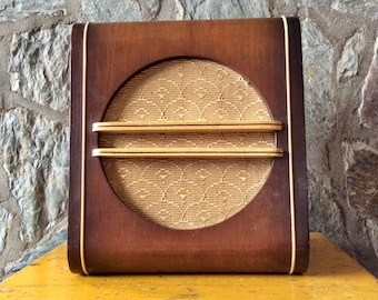 Vintage Deco-style brown wood speaker enclosure or speaker box with beige upholstery fabric speaker cloth in a non-working condition