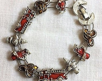 SLIDE CHARM BRACELET fireman or firehouse theme with 10 charms in red and yellow enameling on silver metal. Vintage 1950s collectible.