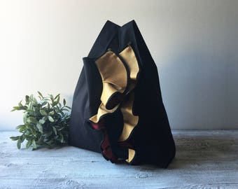 Sculpture bag Special Edition is a handbag made with black cotton and bicolor ruffles yellow and red, chromed metal trim