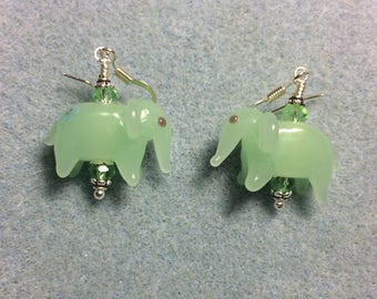 Opaque light green lampwork elephant bead earrings adorned with light green Chinese crystal beads.