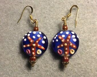 Blue polka dotted and orange lampwork starfish bead earrings adorned with dark orange Czech glass beads.