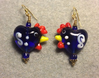 Transparent dark blue with white squiggles heart shaped lampwork hen bead earrings adorned with blue Czech glass beads.
