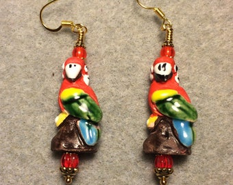 Red, green, yellow and blue ceramic parrot bead earrings adorned with red Czech glass beads.