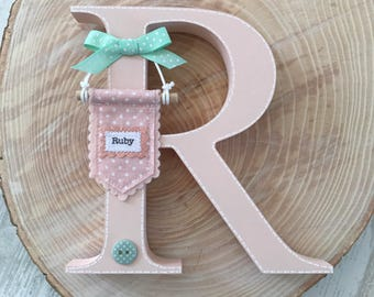 Personalised freestanding wooden letter hand painted in blush pink with mini fabric pennant