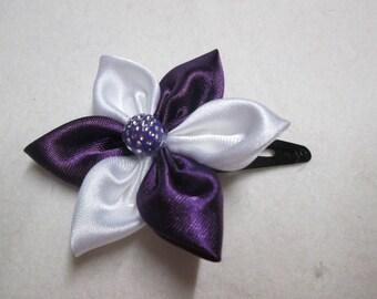 A purple and white satin flower hair clip