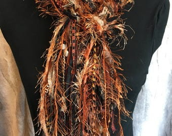 Unique fashion scarf in shades of black, copper, brown, gold and taupe.