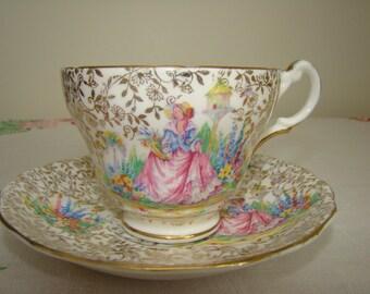 Bone china pink crinoline lady tea cup and saucer 22 karat gold warranted, chintz, lupines, bird house