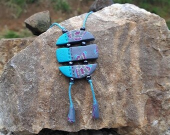 Blue round necklace separated by beads made of polymer clay