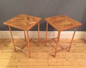 pair of side tables in a retro industrial style with a copper pipe frame and reclaimed oak herringbone/parquet style tops