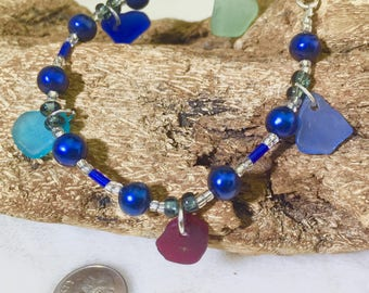 Multi colored Carribean Sea glass bracelet with red, turquoise , mint, cornflower blue and cobalt blue sea glass, blue pearls, other beads.