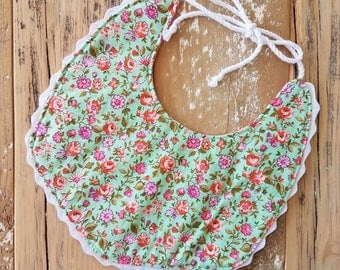 Girl bib, reversible, green floral, coral