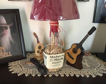 Makers Mark lamp with burgundy shade. Stuffed base of straw. Uniquely different!