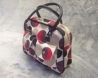 Spot patterned canvas bag in Red, creme, black and beige with brown leather effect handles.